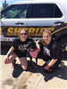 Two Girls with Dog in Front of Police Sheriff Car